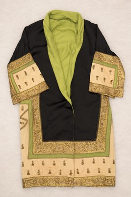 Black satin coat with green, pink, and gold embroidery, front view, 1920