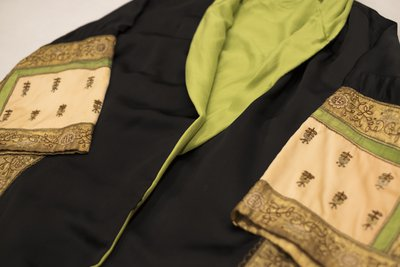 Black satin coat with green, pink, and gold embroidery, cuff detail, 1920