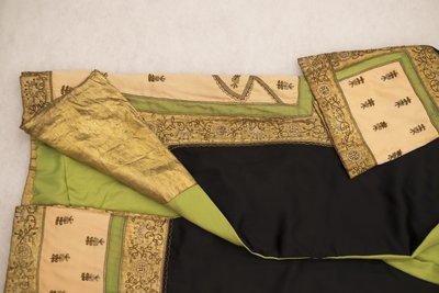 Black satin coat with green, pink, and gold embroidery, side detail, 1920