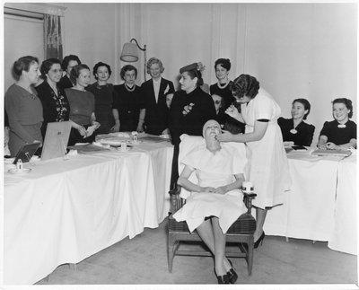Helena Rubinstein applying beauty treatment during beauty school class