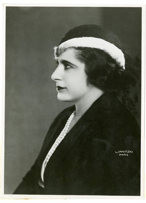 Helena Rubinstein in cloche with light band, dark jacket and rows of pearls