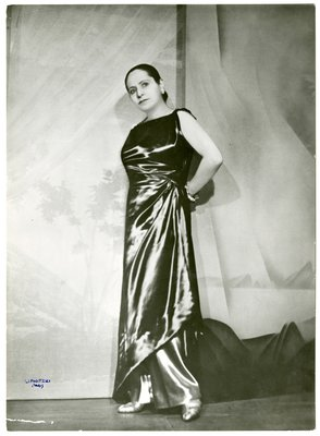 Helena Rubinstein in sleeveless gown with abstract landscape painting