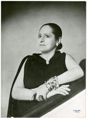 Helena Rubinstein in dark ensemble with cape and jeweled high neckline