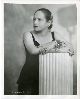 Helena Rubinstein in ensemble with sweetheart neckline, arms on column