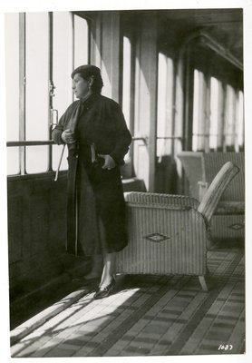 Helena Rubinstein on a ship's deck by rattan chairs