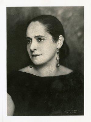Helena Rubinstein in drop earrings and sleeveless ensemble