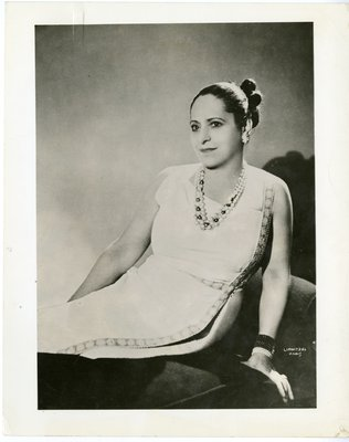 Helena Rubinstein on chaise lounge in embroidered dress by Lanvin