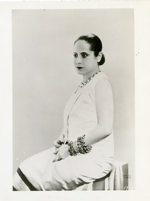 Helena Rubinstein in light sleeveless dress and large bangles