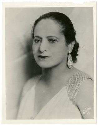 Helena Rubinstein in light V-neck with beaded sleeves and jeweled neckline