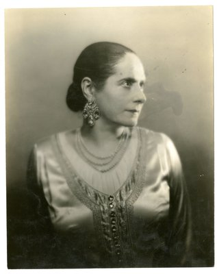 Helena Rubinstein in Schiparelli blouse, pearls, and quatrefoil earrings