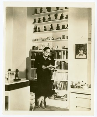 Helena Rubinstein standing with open book