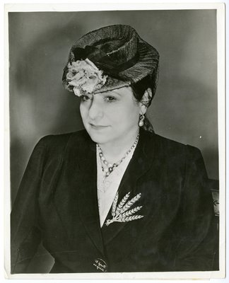 Helena Rubinstein in suit with French text on button and derby-style hat