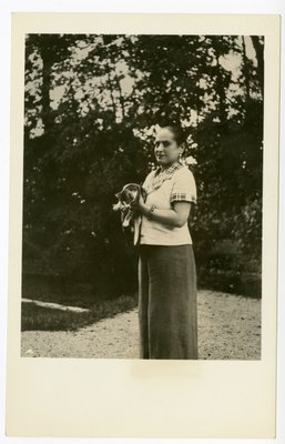 Helena Rubinstein in jacket with plaid trim holding young cat