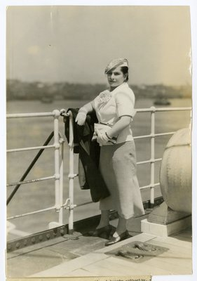 Helena Rubinstein on deck of ship in gingham skirt