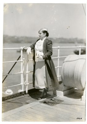 Helena Rubinstein on deck of ship wearing gingham skirt
