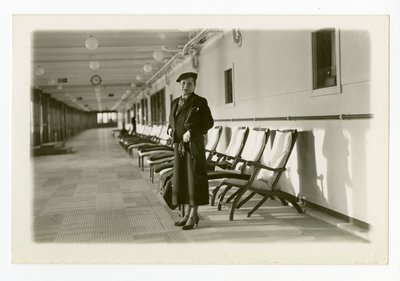 Helena Rubinstein in flat cap and dark ensemble by deck chairs on ship