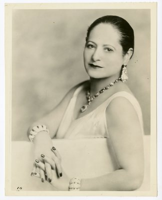 Helena Rubinstein leaning over partition with fingers entwined