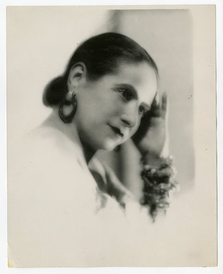 Helena Rubinstein in blurred photograph wearing hoop earrings and bangles