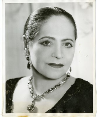 Helena Rubinstein in dark lace and pendant necklace