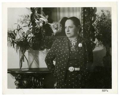 Helena Rubinstein in polka-dot suit with calla lillies
