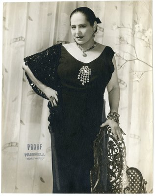 Helena Rubinstein wearing shawl, standing with hand on chair