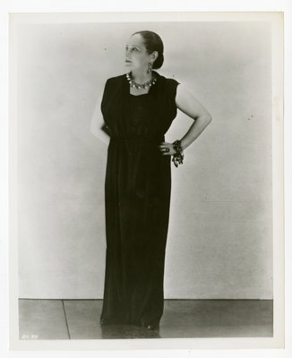 Helena Rubinstein with hands at hips in floor-length ensemble