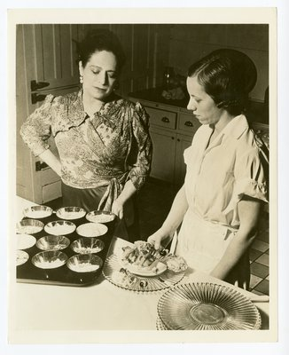 Helena Rubinstein in kitchen with fruited desserts