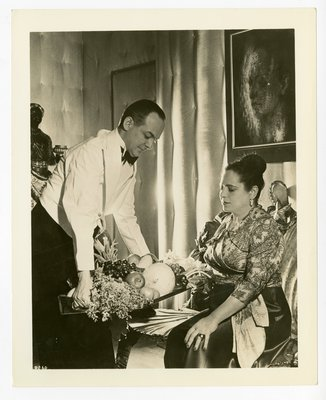 Helena Rubinstein seated below portrait by Tchelitchew