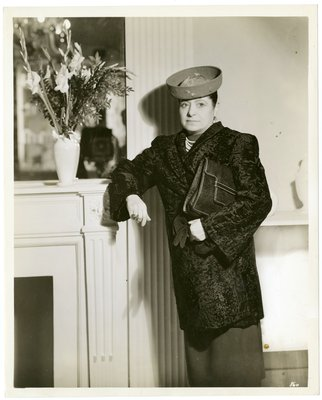 Helena Rubinstein by fireplace in broadtail coat