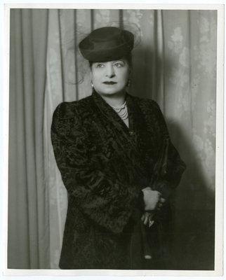 Helena Rubinstein in broadtail coat and hat with netting