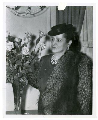 Helena Rubinstein with roses wearing fox jacket