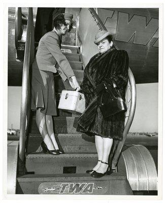 Helena Rubinstein in fur on TWA airplane steps