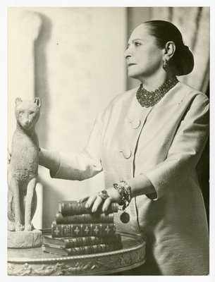 Helena Rubsintein wearing silk shantung with hand on books