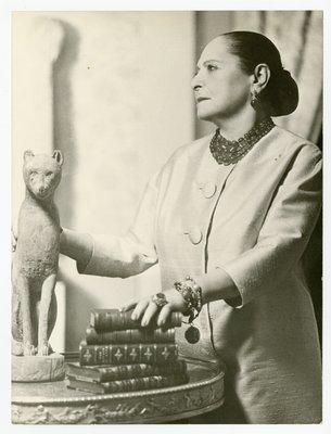 Helena Rubsintein wearing silk shantung with hand on books