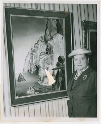 Helena Rubinstein with her portrait by Dali hanging from cord in curtained space
