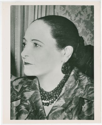 Helena Rubinstein in three-quarter profile in garment with leaf design