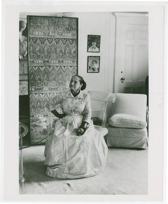 Helena Rubinstein seated with Hindu-themed screen and art