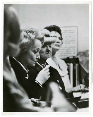 Marlene Dietrich smoking, with Helena Rubinstein looking on at a Christian Dior show