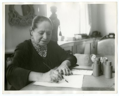 Helena Rubinstein at a desk with calligraphy pen
