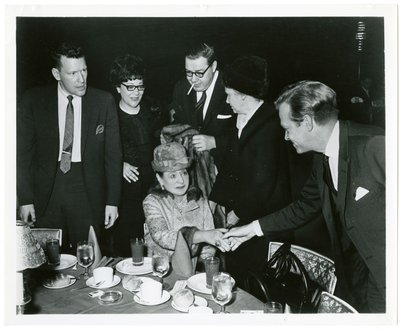 Helena Rubinstein shaking hands with man at dinner