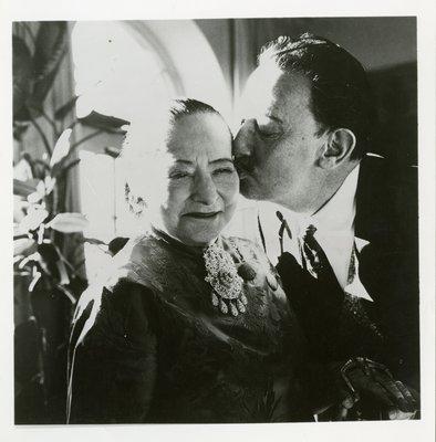 Salvador Dali kissing Helena Rubinstein on the cheek